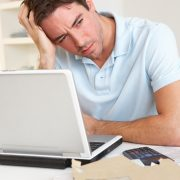 Mann sitter med hodet i hånden ved PC