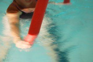 En som padler i vannet med en rød treningspølse