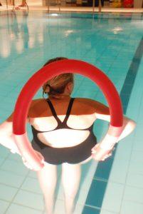 En som står med ryggen til, alene i et basseng med en rød pølle