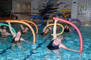 Gruppe mennesker i et basseng trener med fargerike pøller