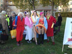 En gruppe damer i badedrakter og slåbrok som demonstrerer