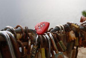 Mange rustne hengelåser og et rødt hjerte-hengelås