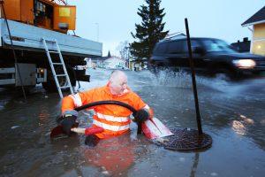 Mann som står med isvann til livet og åpner tett kumlokk