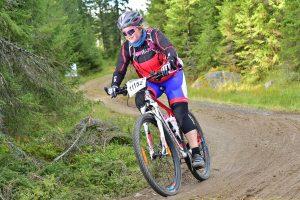 Dame i sykkelutstyr sykler i skogen