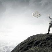 Mann på fjelltopp som øfter vektstang med en hjerne i hver ende