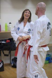 Dame og mann i taekwon-do-klær som ler hjertelig