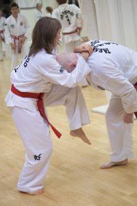Dame som bruker taekwondo-teknikk på en mann