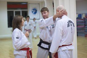 Dame som får instruksjon fra taekwondo-trener