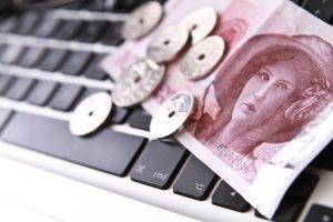 Norske sedler og mynter på et tastatur