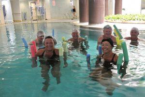 6 personer trener i et basseng med fargerike pøller