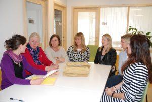 8 damer sitter med en bunke søknader på kontoret til Seksjon for behandlingsreiser