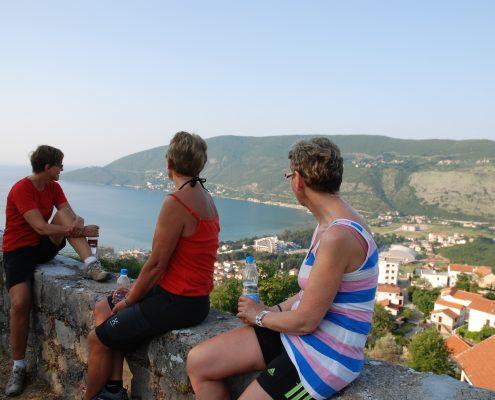 Tre damer i treningstøy sitter på en mur og ser utover Kotorbukta i Igalo