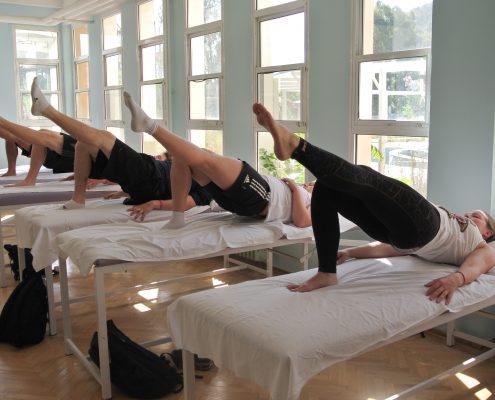 5 personer på treningsbenker som løfter hofter og et ben strakt ut