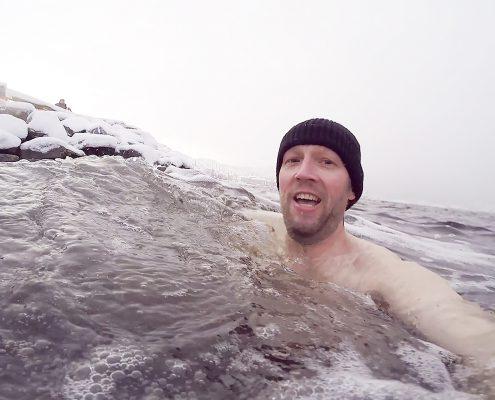 Mann med lue som bader i januar.
