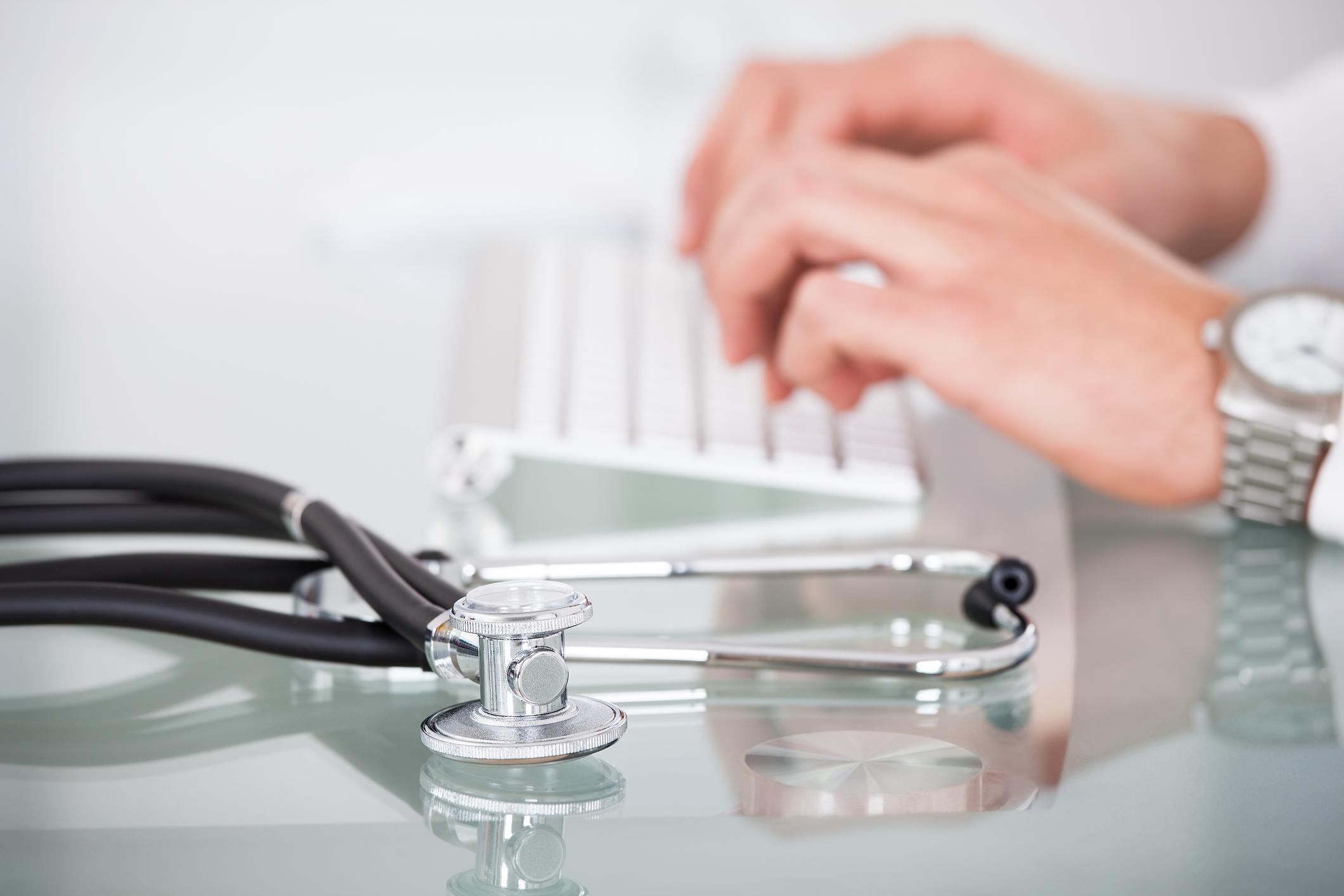 stetoskop, hender som skriver på tastatur