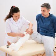 Sykepelier gipser benet til en mann