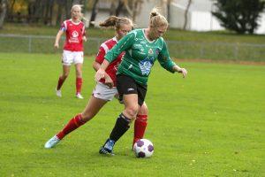 Kvinnlig fotballspiller i grønn drakt dribler en motspiller i rød drakt