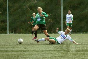 Kvinnlig fortballspiller hopper over en motspiller som ligger på bakken