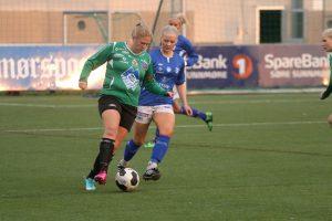 Kvinnlig fotballspiller dribler en motspiller
