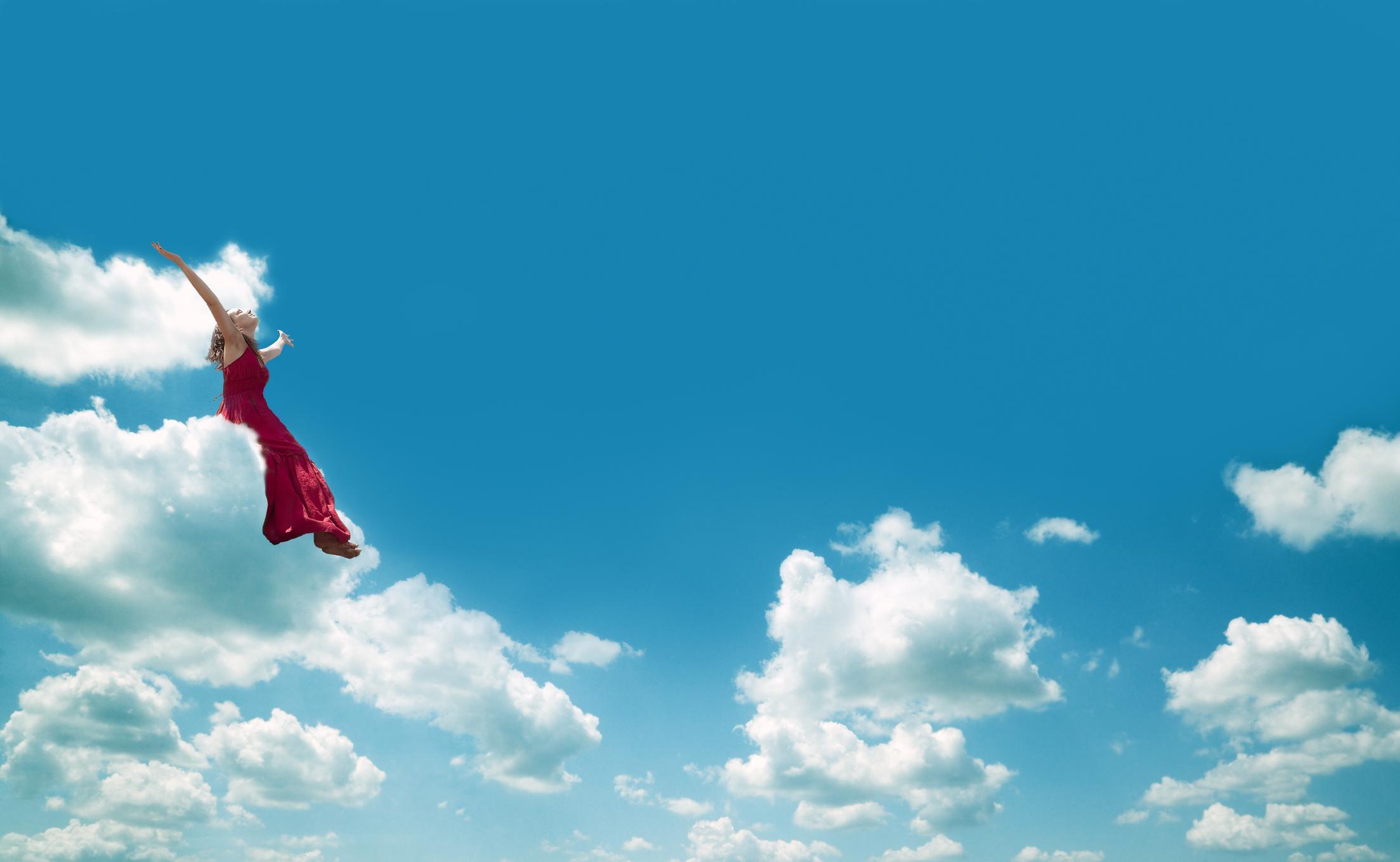 Dame med rød kjole som flyr mellom hvite skyer på blå himmel