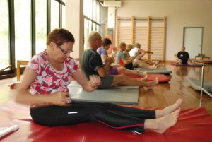 Fler emennesker i en gymsal, som trener sittende på baken.