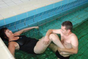 Dame blir tøyd og strukket av fusioterapeut i et basseng