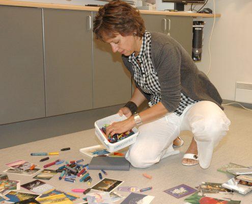 Dame med boks med fargestifter og mange fargerike kort utover gulvet