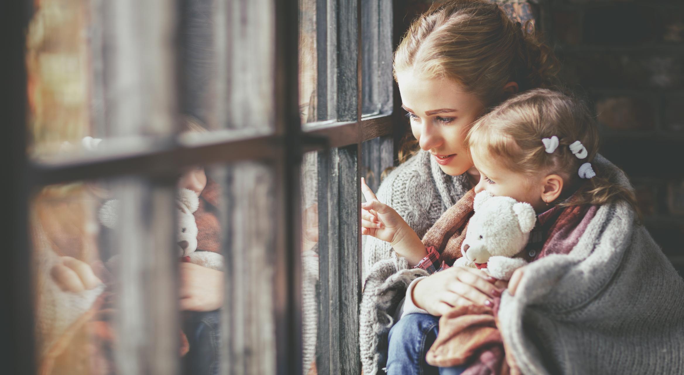 Mor og datter med pledd rundt seg ser ut av vinduet