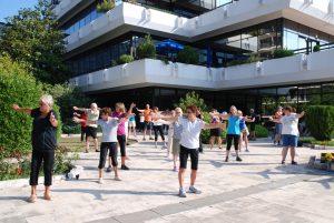 Gruppe som står utendørs med armene ut og puster og vrir kroppen med armene ut