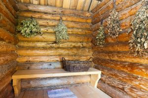 Innsiden av en gammel badstue med bjerkeris hengende på veggene.