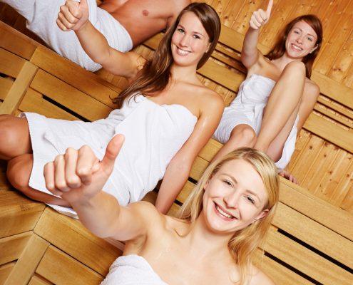 Fire mennesker med hvite håndklær i en badstue