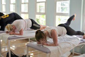 """Camilla Aure og en medpasient står """"Planken"""" på behandlingsbenker i gruppegym"""