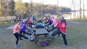 En gjeng mennesker i treningstøy som tøyer ut bena på piknikbord i naturen