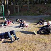 Gruppe mennesker ligger på bakken med treningsstrikk over bena