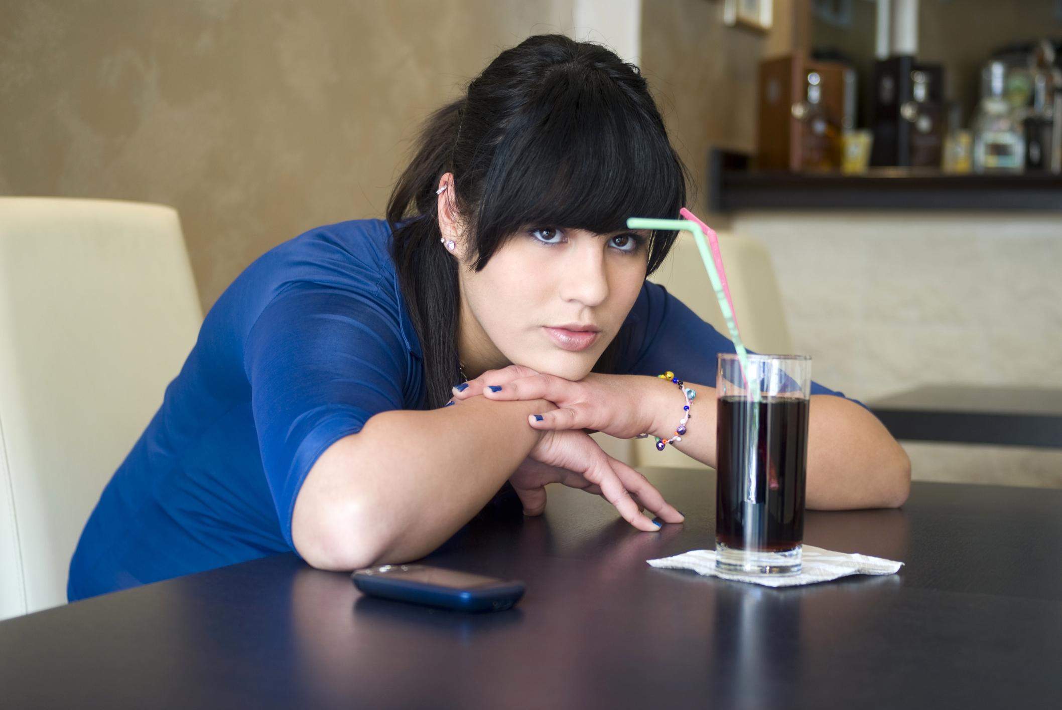 Ung kvinne sitter ved et bord og ser bekymret ut