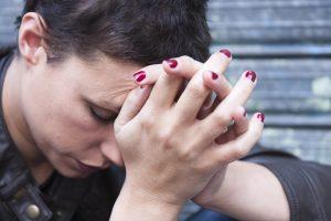 Ung kvinne sitter med hodet i hendene
