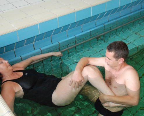 Dame får individuell fysioterapi i basseng
