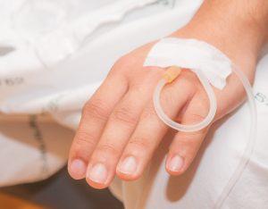 Hånd med intravenøs medisin tapet fast