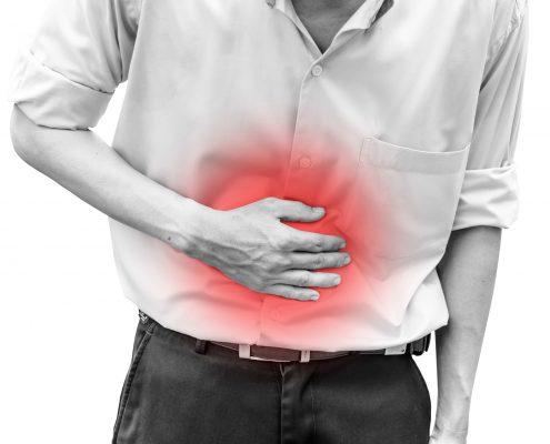 Svarthvitbilde av mann som holder seg på magen, markert med rødt