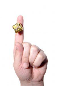 Hånd med pekefinger i være med en minipakke festet på fingeren