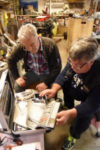 To menn sitter og ser på gamle bilder i en koffert