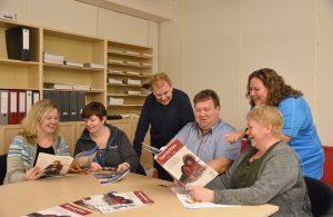 Bilde av styret i SpAfo Norge og redaktøren sitter rundt et bord og ser gjennom utgaver av Spondylitten