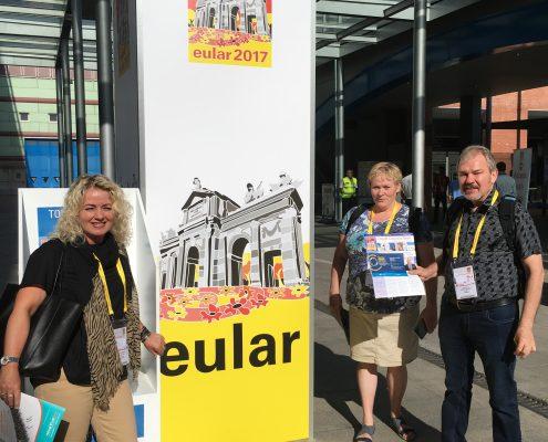 Tre personer ved et banner med EULAR-logoen på
