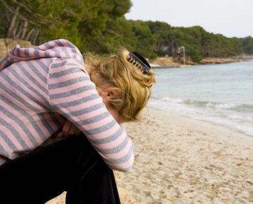 Ung kvinne sitter smamenkrøket og deprimert på strand