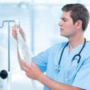 Mann som henger opp en intravenøs behandling på stang