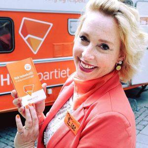 Lise Askvik med partiprogram foran en oransje campingvogn