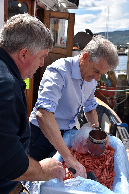Jarle Granum og Jonas Gahr Støre måler opp reker i et literbeger