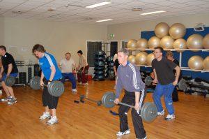 Menn som løfter vekter i treningssal
