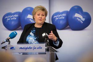 Erna Solberg på talerstol med Høyre-logo bak