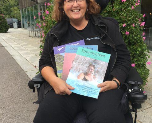 Kvinne i rullestol med Spondylitten-blader i en vifte i fanget